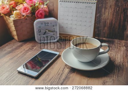 Cup Of Coffee With Desktop Calendar 2019,smart Phone,clock And Pot Of Rose Flower On Blue Wooden Des