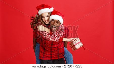 Happy Cheerful Couple Black Man And Caucasian Woman In Christmas Hats On Red Background