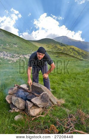 Man kindle the firewood in tourists camp