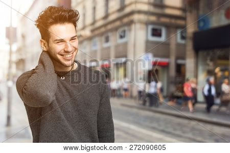 Smiling handsome man walking in the city