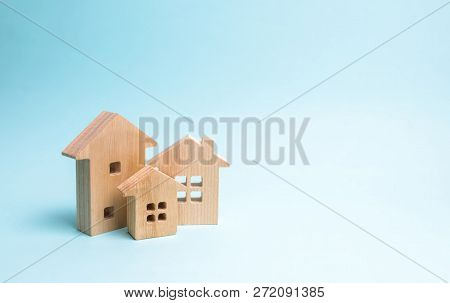 Wooden houses on a blue background. Wooden Toys. The concept of real estate and ownership, the purchase and sale of property. Farm, city, village, enterprise. Construction and improvement of buildings poster