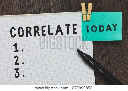 Writing note showing Correlate. Business photo showcasing have mutual relationship or connection in which one thing affects Open notebook page pins holding reminder marker wooden background. poster
