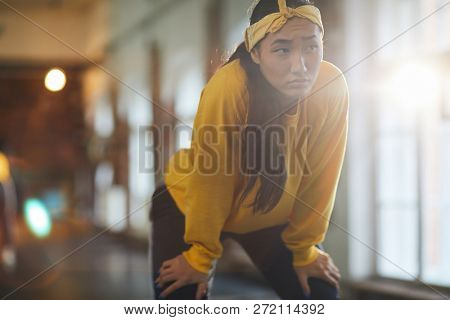 Young pensive woman in activewear scowling at break between hip hop trainings