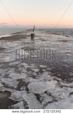 An Icy Pier Leading To A Lighthouse On A Lake At Sunset.  Sheboygan, Wisconsin, Usa.