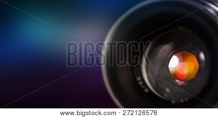 Professional camera lens with reflections and bokeh background.