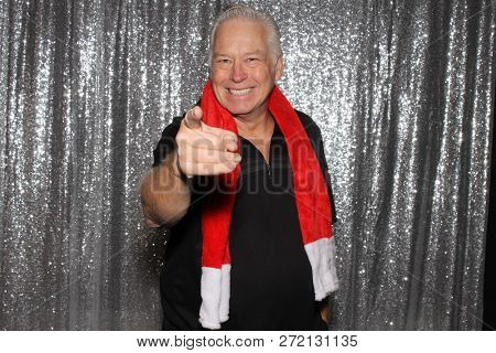 Man in a Photo Booth. A handsome man poses in a Photo Booth with a Silver Sequin Backdrop while wearing a red Christmas scarf. Man smiling for a photo.