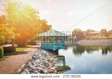 garden park with pavilion on river side in sunny day / waterfront pavilion blue and pathway in the public park