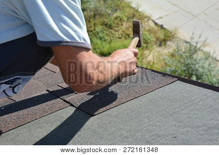Roofer Installing Asphalt Shingles On House Roofing Construction Roof Corner With Hammer And Nails.