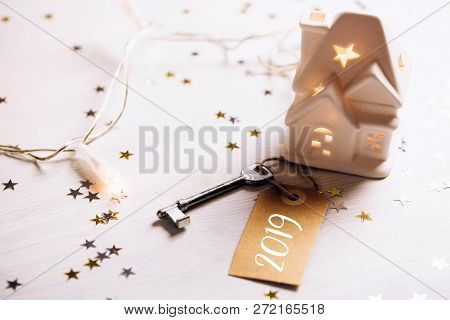 Small Toy White House With A Roof, Lights And Key Standing On Wooden Background With Sparkles. Space