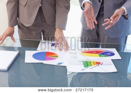 Hands of business people working on statistics in a meeting room