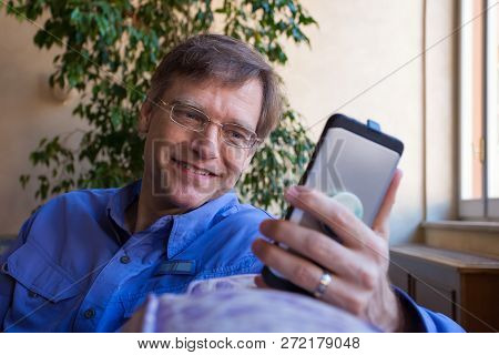Caucasian Man In Forties In Blue Shirt Sitting On Sofa, Smiling And Looking At Smartphone Near Sunny