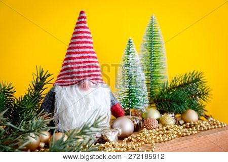 A Christmas decoration with a gnome on a wooden box and yellow background