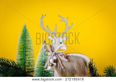 A Christmas decoration wooden reindeer with fir trees on yellow background
