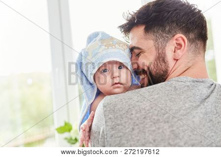 Happy father holds baby with towel around head in arm after bathing