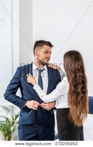 girlfriend fixing boyfriend jacket before work, gender stereotypes concept poster
