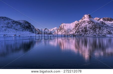 Beautiful Snow Covered Mountains And Colorful Sky Reflected In Water At Dusk. Winter Landscape With
