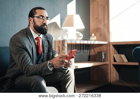 Bearded man wearing business attire feeling concerned before negotiation poster