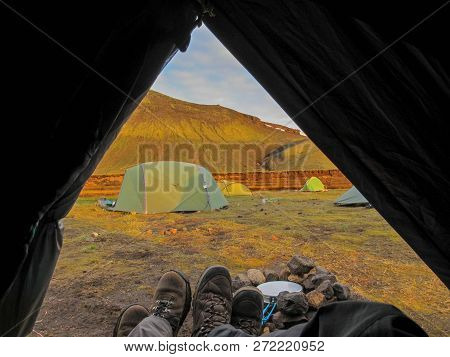 Tent Lookout With Couple Hiking Boots And Mountain View At Sunset. View From Inside A Tent At Sunset