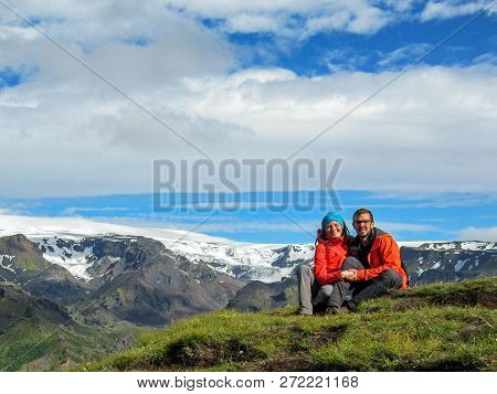 Happy Couple Hugging Sitting On The Stone In The Icelandic Highlands And Admire The Scenery View Wit
