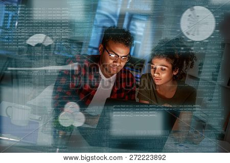 Young Concentrated Indian Data Analysts Looking Over The Data
