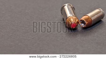 A 40 caliber hollow point bullet and a 44spl red tipped bullet laying together on a gray background with room for text poster