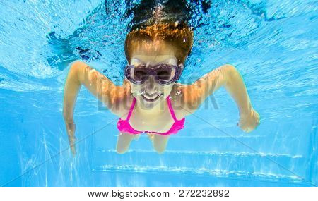 Smiling little girl in swim goggles swimming underwater in pool. Teenage girl diving underwater