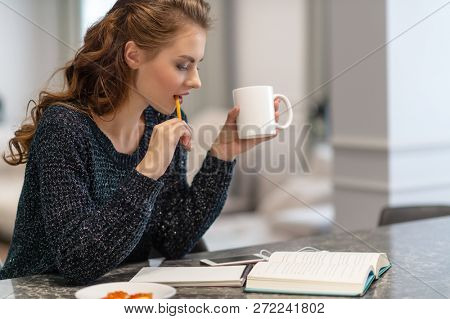 Ideas for business. Studying and working at home. Thoughtful young woman making notes using notepad in kitchen.