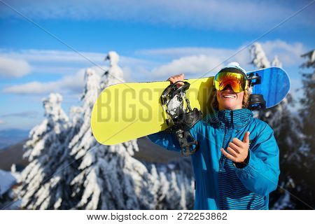 Smiling Snowboarder Posing Carrying Snowboard On Shoulders At Ski Resort Near Forest Before Freeride