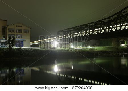 nocturnal view of a railroad bridge over a river poster