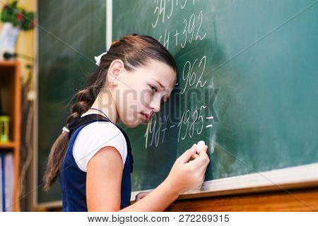 Child Standing Near The Blackboard In School With A Sad Face. Adolescent Learning Difficulties