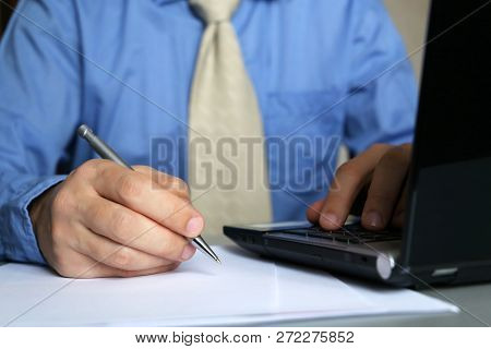 Man In Blue Shirt And Tie Works In Office, Sitting At A Table With Laptop And Pen In Hand. Male Hand