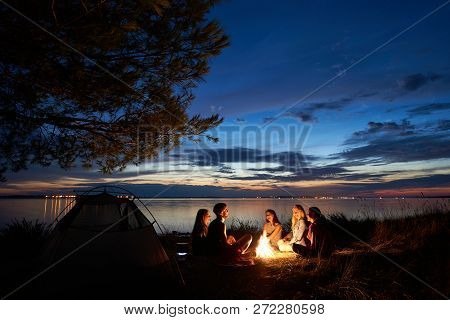 Night Summer Camping On Sea Shore. Group Of Young Tourists Sitting, Laughing In High Grass Around Bo