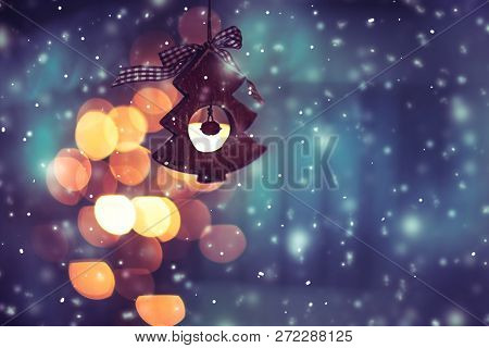 Beautiful Christmas decor, little wooden decorative Christmas tree over blue glowing and snowing background, Merry Christmas greeting card