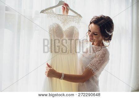Pretty Brunette Bride In Silk Dressing Gown And Lacy Veil Holding Wedding Dress On A Hanger Near The