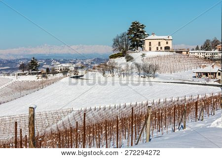 View of rural houses and vineyards on snowy hills under blue sky in Piedmont, Northern Italy.