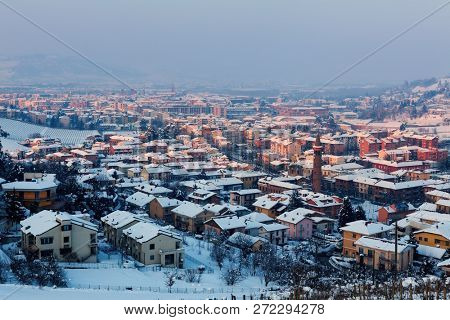 View from above on small italian town of Alba covered with snow in Piedmont, Northern Italy.