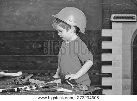 Toddler On Busy Face Plays At Workshop Near Table With Tools. Workshop And Tools Concept. Kid Boy Pl