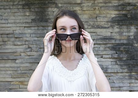 Close-up Portrait Of Pretty Teenager With Beautiful Blue Eyes. Lovely Female Taking Off Eyeglasses A