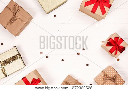 Christmas Craft Gift Boxes With Glitter Create Round Frame On White Wooden Background. Place For Tex