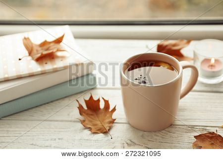 Cup of tea, autumn leaves and stack of books on windowsill poster