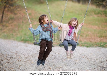 cheerful children are having fun on a swing little brother and sister playing outside