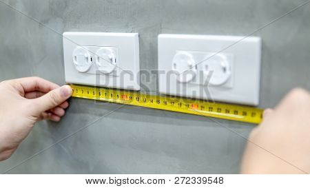 Male hand electrician using tape measure for measuring dimension of electrical outlet with safety cover on the wall. Electrical fixture installation and building construction concepts poster
