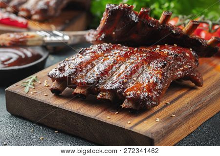 Closeup Of Pork Ribs Grilled With Bbq Sauce And Caramelized In Honey. Tasty Snack To Beer On A Woode