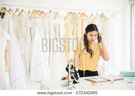 Portrait Of Asian Woman Working And Using Mobilephone In Wedding Dress Store,beautiful Dressmaker In
