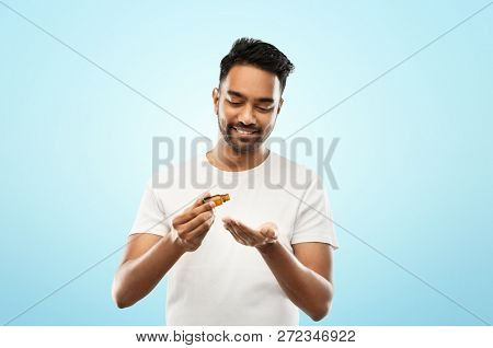 grooming, aromatherapy and people concept - smiling young indian man applying essential oil to his hand over blue background poster