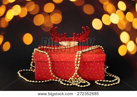 A Christmas decoration gift box with hidden reindeer figure on black background with bokeh lights