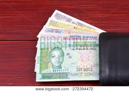 Guinean Money In The Black Wallet On A Wooden Backgrund