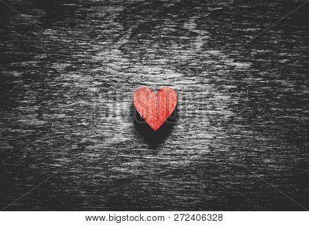 Red wooden heart on black wooden background. Love symbol. Valentine's Day.