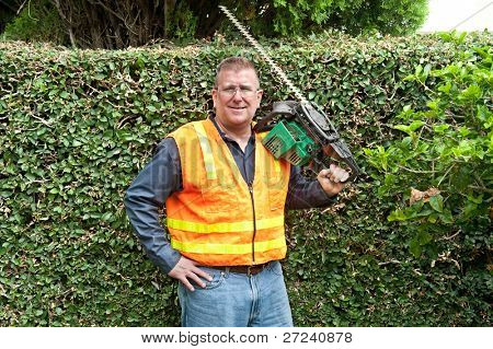 A man conducting his chores by trimming vines along a wall.