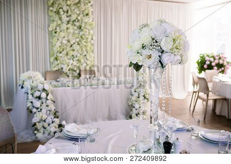 Wedding Table In Restaurant Decorated With Flowers. White Tablecloth, Crystal Glasses And Cutlery, N